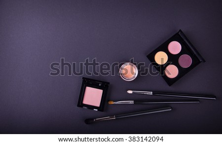 Make up essentials. Set of professional make up brushes, creams and shadows in jars on dark background. Place for your text or logo. Ideal for beauty blog. - stock photo