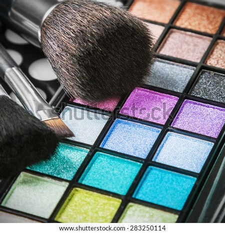 Make-up eyeshadow palettes with makeup brushes. Focus in the middle of the frame on the blue shadows. Shallow depth of field - stock photo