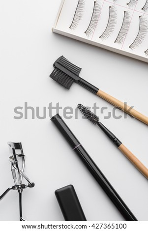 Make-up instruments in the foreground. Special professional tools for eyes every girl needs to have. Accurate row of beauty accessories as brushes, curler, pencil for brows and false eyelashes. - stock photo