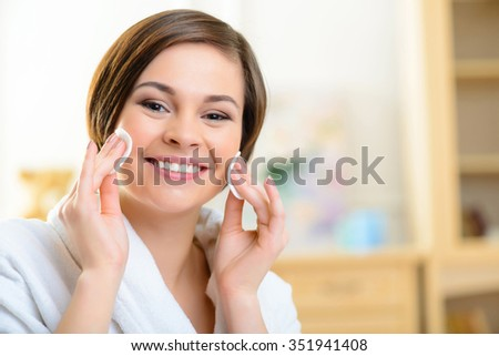 Make up removal. Young teenage smiling girl is using cotton pads to remove her make up. - stock photo