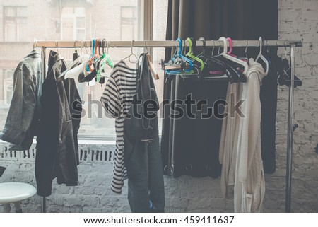 Make up room or dressing room with clothes hanging on hangers.