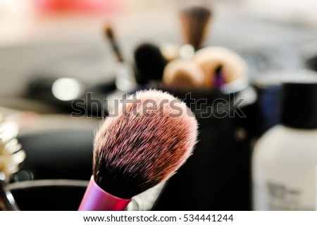 make up set, Professional makeup brushes in tube. Dirty makeup tools, soft makeup brushes and maskara on black background