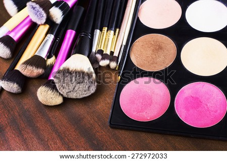 Make-up tools, brushes and shadows on a wooden background