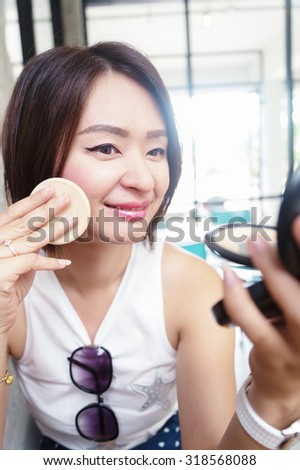 make up woman holding powder puff