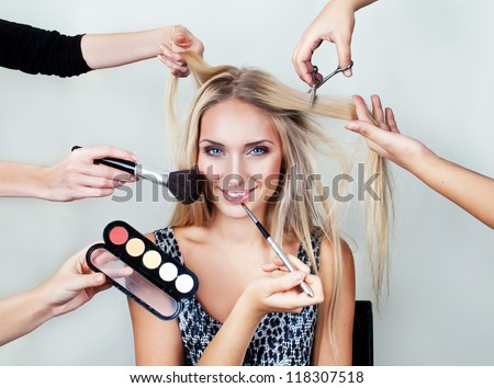 make up woman with many hands. makeup brushes, scissors, shadows. - stock photo