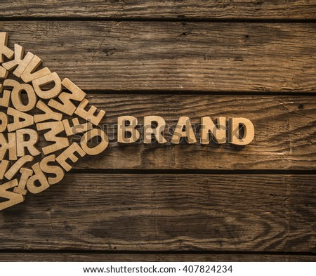 "Make your own brand. The word ""Brand"" is lined with wooden letters on wood planks of table. Photo image"