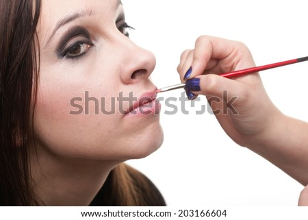 Makeover beautiful young brunette woman applying lips make-up zone isolated background - stock photo
