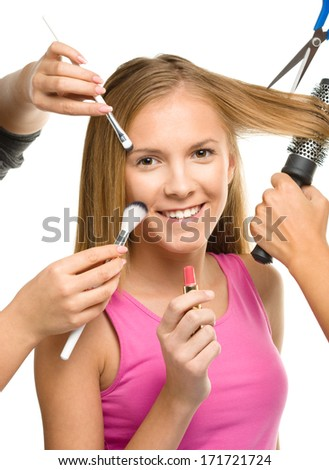 Makeover process of a young teen girl, few hands are helping to apply makeup and cut hair, isolated over white - stock photo