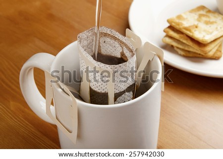 makes coffee by drip brew with cookie and woody table  - stock photo
