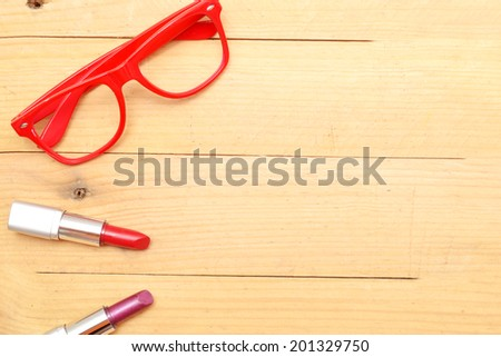 Makeup and glasses on wood - stock photo