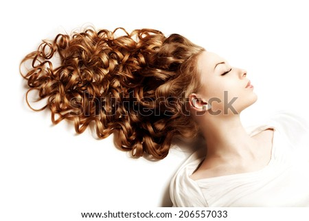 Makeup and hairstyle. Young beautiful woman with luxurious curly hair. Modern stylish trendy girl with curls, long groomed hair healthy