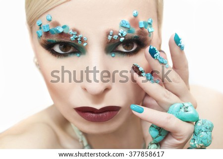 Makeup and manicure with blue and brown lacquer decorated with beads and turquoise.