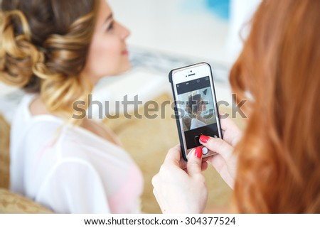 Makeup artist and hair stylish making photo of beautiful bride on her smart phone