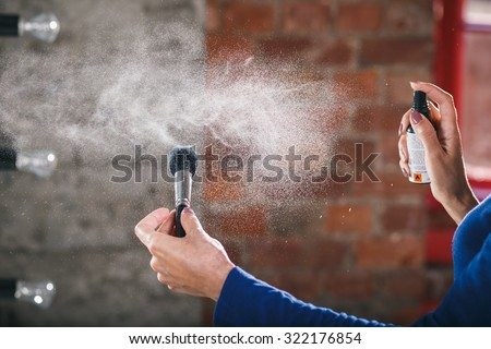 Makeup artist and her workplace: cleaning of the brush by cleaning spray. Woman and cosmetics.  - stock photo