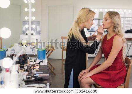 Makeup artist applies lipstick. Beautiful woman face. Perfect makeup - stock photo