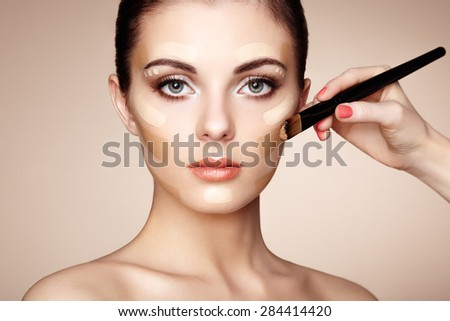 Makeup artist applies skintone. Beautiful woman face. Perfect makeup. Skincare foundation - stock photo