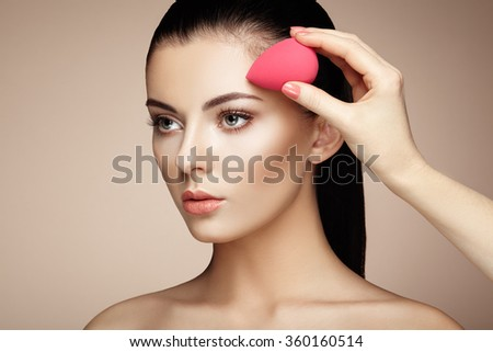 Makeup artist applies skintone. Beautiful woman face. Perfect makeup. Skincare foundation. Sponge makeup artist - stock photo