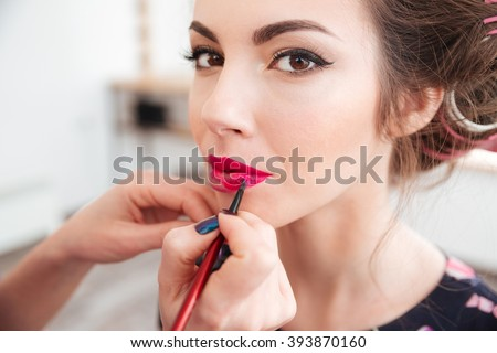 Makeup artist applying bright pink lipstick to lips of young woman in curlers - stock photo