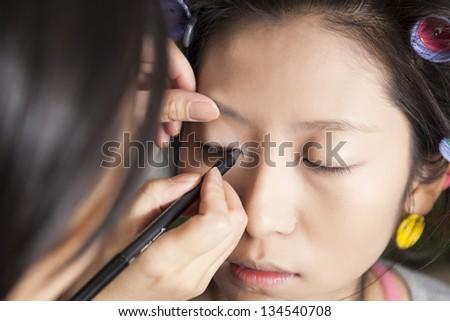 Makeup artist applying eye makeup on a woman's face. - stock photo