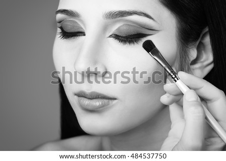 Makeup artist applying eye shadow. Black and white