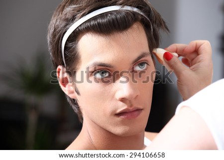 makeup artist applying foundation with a brush, man in the dressing room mirror - stock photo