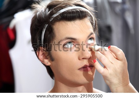 makeup artist applying foundation with a sponge, man in the dressing room mirror - stock photo