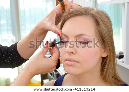 Makeup artist applying mascara on attractive womans eyes in salon - stock photo