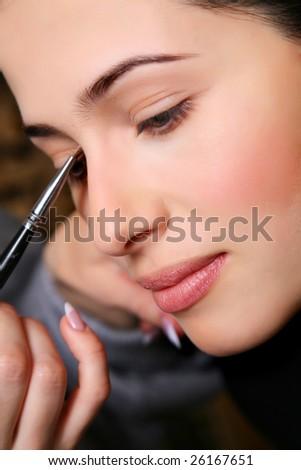 makeup artist applying mascara on the eyelashes of a beautiful girl. - stock photo