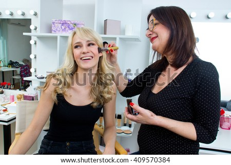 Makeup artist at work on a woman model in beauty salon