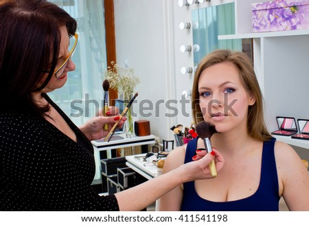 Makeup artist at work on a woman model in beauty salon - stock photo