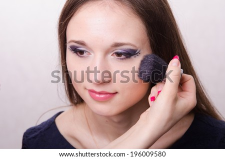 Makeup artist brush powder gets on the face of a beautiful young girl in the makeup