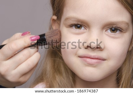 Makeup artist deals powder brush on the face of a five year old girl