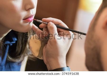 Makeup artist doing lips makeup with a brush to pretty woman