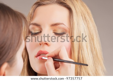 makeup artist doing lips makeup with a brush to young blonde woman - stock photo