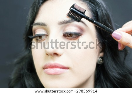 makeup artist doing make up using cosmetic brush applying eye shadow on the eyelids for beautiful arabian and mixed race woman at beauty salon with black background - stock photo