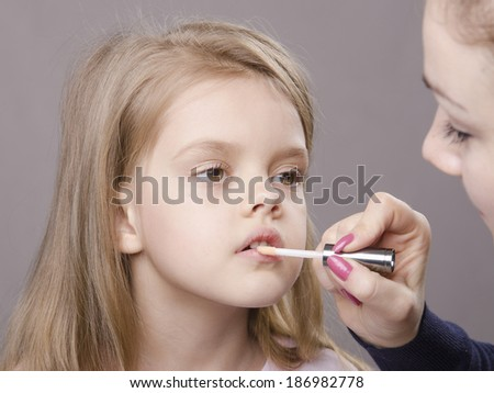 Makeup artist in the process of makeup causes Shine on the lips five year old girl