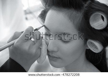 makeup artist is applying cosmetics on model face.