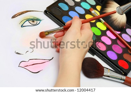 Makeup artist is sketching makeup style on a paper.