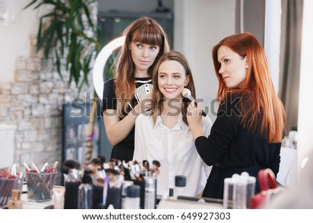 Makeup artist makes evening bright make up for model. Stylist makes hair hairstyles blonde European model. Beauty lifestyle concept.