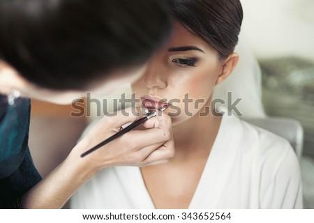 makeup artist makes young beautiful bride bridal makeup - stock photo