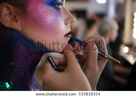 Makeup artist paints her lips. Young attractive blonde girl in bright art-makeup.