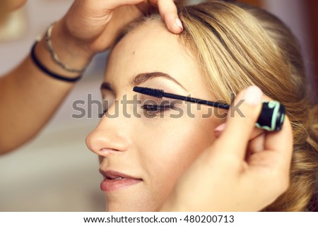 Makeup artist preparing bride before the wedding in a morning. Beautiful bride portrait wedding makeup.