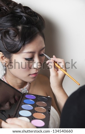 Makeup artist use a brush applying eyeshadow on a woman's face. - stock photo