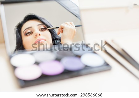 makeup artist woman doing make-up using cosmetic brush and mirror applying eye shadow on the eyelids for yourself at beauty salon with white background - stock photo