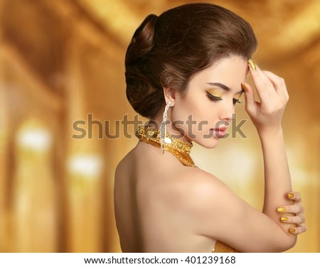 Makeup. Beautiful fashion woman in gold, elegant lady in expensive pendant  jewelry close-up. Beauty Hairstyle.  - stock photo