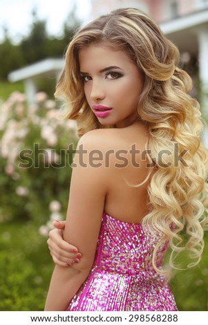 Makeup. Beautiful girl with blond long wavy hair posing in Fashion dress, attractive model in blossom park. - stock photo