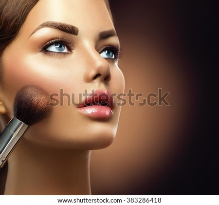 Makeup. Beauty model girl Applying Make-up  closeup. Cosmetic Powder Brush for Make up. Female with Perfect Skin. Blue eyes, Pink Lipstick. Isolated on Black Background. Beautiful woman face, Makeover - stock photo