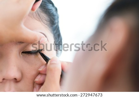 makeup beauty with brush eye liner on pretty woman face