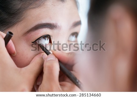 makeup beauty with brush eye liner on pretty woman face - stock photo