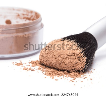 Makeup brush against the background of jar with loose cosmetic powder on white background